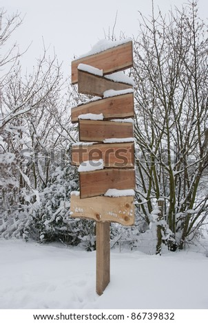 Blank wooden signpost covered in snow on a winter day.