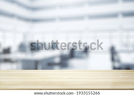 Blank wooden tabletop with bright furnished office on background, mockup