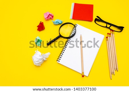 Blank writing pad for ideas and inspiration on colored background.Magnifying glass on top of notepad.Around the notepads lies lot crumpled paper.
