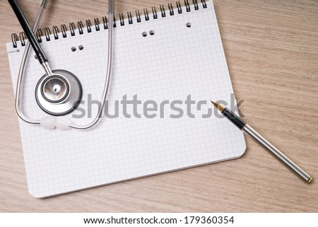 blank writing pad with pen and stethoscope on a table / blank writing pad