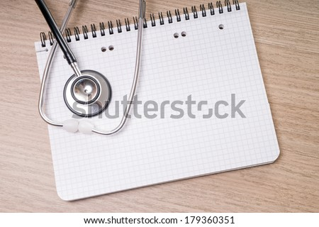 blank writing pad with stethoscope on a table / blank writing pad
