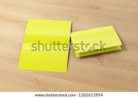 Blank yellow open and folded half-folded flyer leaflet on wooden background. With clipping path around brochure. 3d illustration