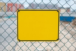 blank yellow sign on construction site fence - warning sign mockup