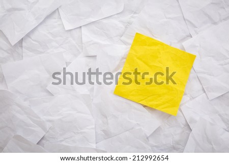 blank yellow sticky note against background of white crumpled notes