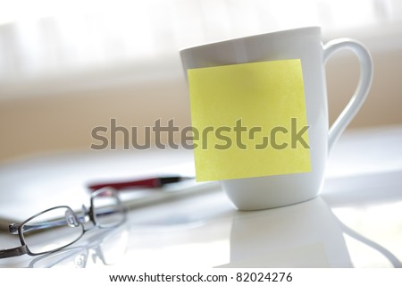 Blank yellow sticky note on a coffee cup ready for message