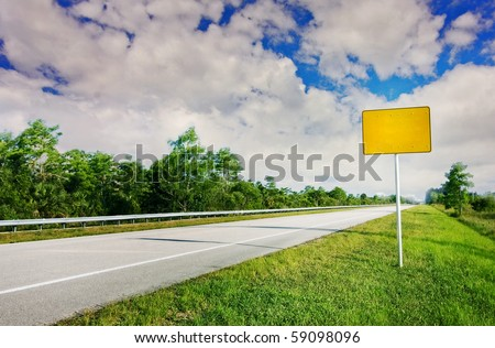 Blank yellow traffic sign by the highway road going through a natural landscape