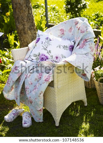Blanket and cushion with floral pattern on garden chair
