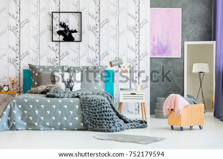 Blanket in wooden box in monochromatic bedroom with deer clock above king-size bed #752179594