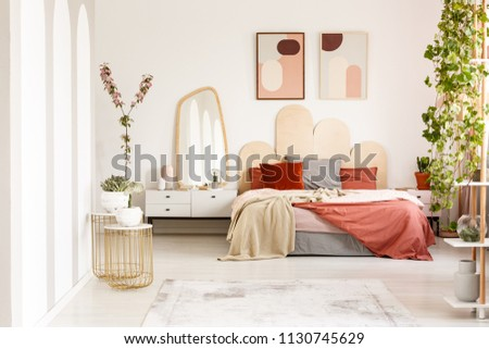 Blanket on bed with headboard under posters in modern bedroom interior with plants. Real photo #1130745629