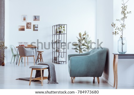 Blanket on bench and grey armchair in bright room with chairs at dining table against wall with gallery