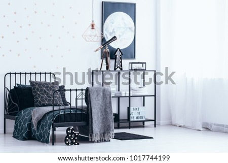 Blanket on black bed with dark bedsheets against the wall with gold stars next to a shelf with telescope in bedroom interior
