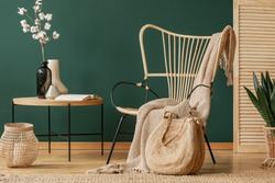 Blanket on rattan armchair next to table with flowers in green flat interior with lantern. Real photo