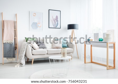 Blankets on a ladder and white table on a carpet in living room with lamp and cushions on a sofa #756043231