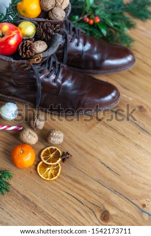 Blankly cleaned boots with sweets, nuts and apples to santa nikolaus gift, wooden floor