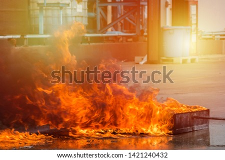 Blaze fire flame in container with sunlight, Fire extinguisher training in industrial factory. #1421240432