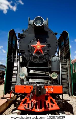 blck steam locomotive on a background of blue sky - stock photo