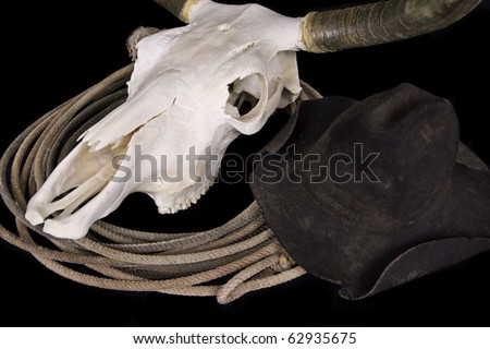 Bleached out Texas longhorn steer skull, well used cowboy hat and lasso on black background.