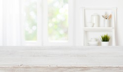 Bleached wooden table top on blurred kitchen summer window background