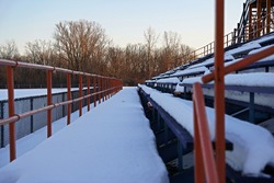 Bleachers covered with snow contrasting winter and summer.