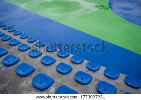 Bleachers of an outdoor basketball court, with blue plastic seats for the spectators