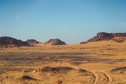 bleak desert landscape of reddish sands with mountain and rock formations in northern Saudi Arabia