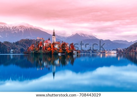 Bled lake in Slovenia, famous and very popular landmark and travel destination. Night scene of island with ancient church in the middle of Bled lake. Romantic place, sunset dusk scenery. Fall season.