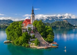 Bled, Slovenia - Aerial drone view of beautiful Lake Bled (Blejsko Jezero) with the Pilgrimage Church of the Assumption of Maria and Bled Castle and Julian Alps at backgroud on a bright summer day