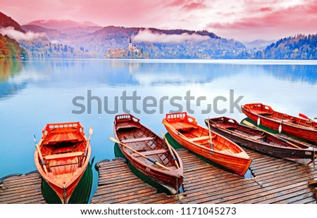 Bled, Slovenia. Great Slovenian nature - lake Bled in fall season. Amazing landscape - traditional Pletna boats at autumn background. Lake bled is famous place and popular European travel destination.