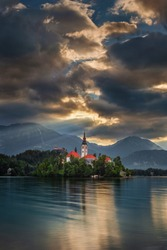 Bled, Slovenia - Lake Bled (Blejsko Jezero) with the Pilgrimage Church of the Assumption of Maria, Bled Castle and Julian Alps at background on a summer morning. Sunbeam shining through in clouds