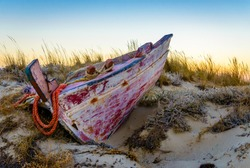 Bleeding body. An abandoned boat at Plaka beach, Naxos, Greece, in the dusk.