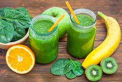 Blended green smoothie with ingredients selective focus