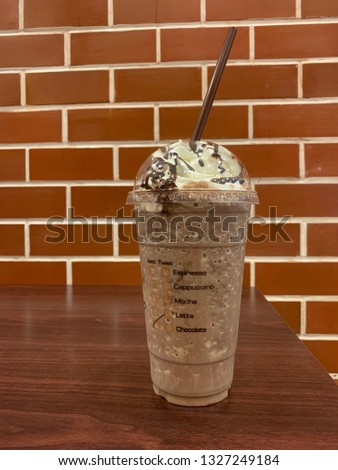 Blended ice chocolate in plastic glass on the wooden table #1327249184