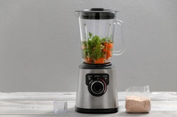 Blender, carrot, parsley, dill on a gray wooden table. Girl makes a smoothie of vegetables. Healthy lifestyle. Dietary nutrition. Carrots and greens close-up.