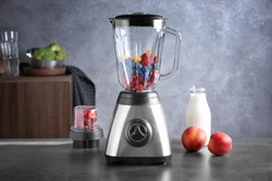 Blender with berries on table