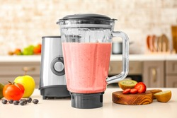 Blender with healthy smoothie on kitchen table