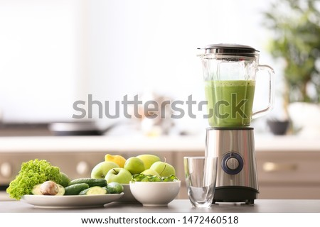 Blender with tasty smoothie and ingredients on table in kitchen #1472460518