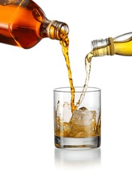 Blending whiskey concept, pouring two kind of whiskey in a glass with ice cubes