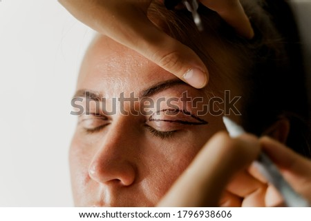 Blepharoplasty markup close-up on the face before the plastic surgery operation for modifying the eye region of the face in medical clinic. 2 doctors do plastic cosmetic operation Stock photo ©