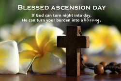 Blessed ascension day. God can turn your burden into a blessing as He can turn night into day. Ascension day of Jesus Christ message concept with holy cross crucifix closeup, rosary beads and flowers.