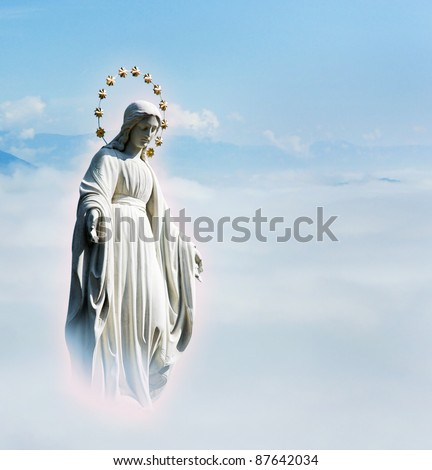 Blessed Virgin Mary at the sky background. Mother Mary statue. Holy phenomenon of Holy Maria in the light of glow in the sky above the clouds.