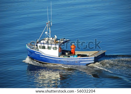 Bleu Fishing boat heading out to the ocean in the early morning - stock photo