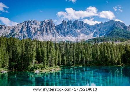 Photo of  bleu lake in the dolomites Italy, Carezza lake Lago di Carezza, Karersee with Mount Latemar, Bolzano province, South tyrol, Italy. Landscape of Lake Carezza or Karersee and Dolomites in background