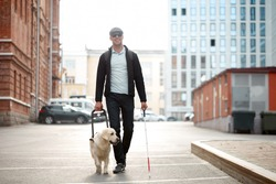 blind caucasian man guided by puppy. pet icon sign or symbol. guy with companion friend in city streets