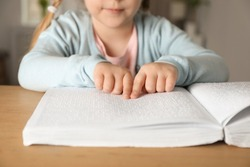 Blind child reading book written in Braille at table, closeup