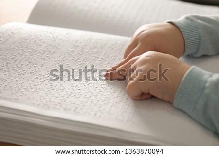 Blind child reading book written in Braille, closeup #1363870094