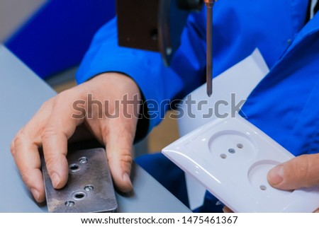 Blind man assembler, electrician hands assembling electric socket at fabric. Repair, production, handmade manufacturing process, electricity and disabled people concept