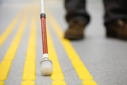 Blind pedestrian walking and detecting markings on tactile paving with textured ground surface indicators for blind and visually impaired. Blindness aid, visual impairment, independent life concept.