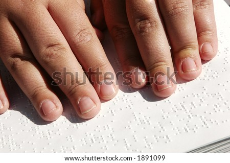 Blind person reading Bible written in Braille