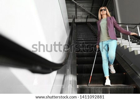 Blind person with long cane on escalator indoors Foto stock ©