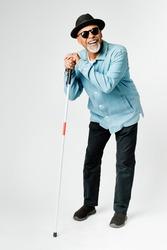 Blind senior man with a cane walking